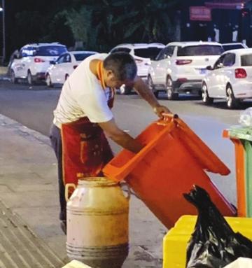 用炒菜勺舀垃圾桶里油的男子。