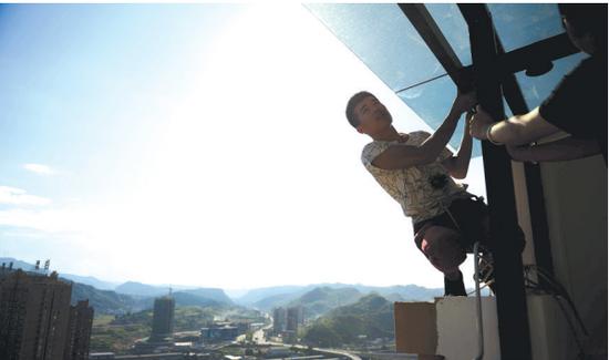 一栋高层建筑上,唐杰在查看玻璃安装情况。