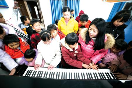 卢小卜教孩子们弹钢琴。