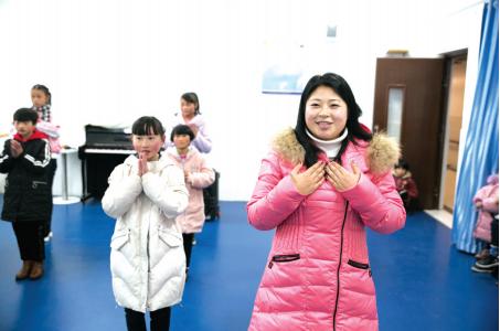 卢小卜在教孩子们表演舞蹈《感恩的心》。