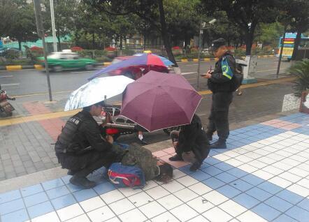 民警为伤者撑伞挡雨。
