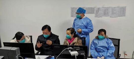 王万灵(左二)与医护人员讨论疫情医疗救治方案