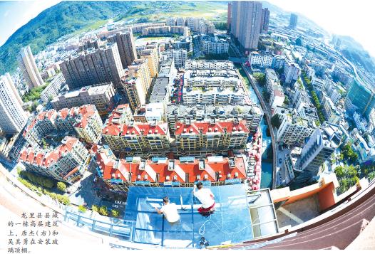 龙里县县城的一栋高层建筑上,唐杰(右)和吴其勇在安装玻璃顶棚。