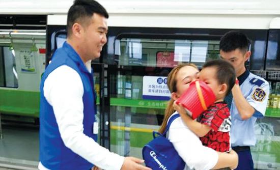 工作人员将走失的孩子交还给妈妈。 张泽媛 刘炯 摄