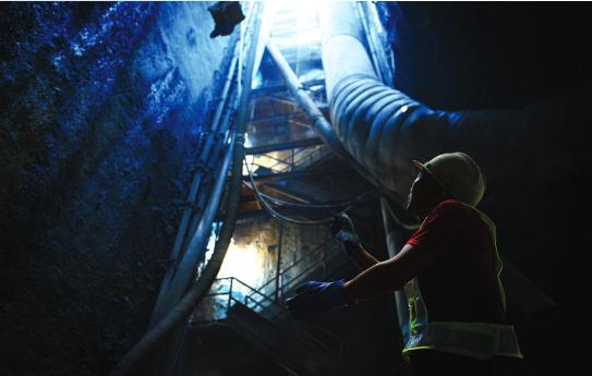 一位工人在24米深的井口悬挂吊机绳索。(资料图)