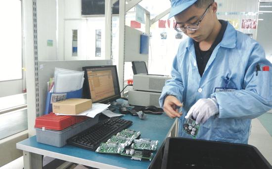 贵阳永青仪电科技有限公司员工将初步检测过的芯片板放入塑料盒