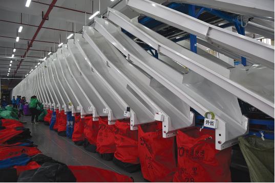 中通快递自动分拣线上工人将分拣好的包裹装袋打包。