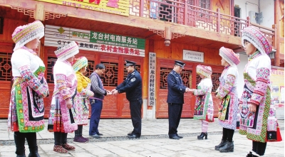 李德强(右边着警服者)与民警向苗乡群众发放警民联系卡。