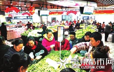 市民们在合力惠民生鲜超市花果园R区店抢购豌豆角。