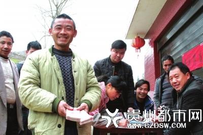 2018年2月9日,白茶基地向农民工发放2017年11月和12月工资,村民邹书举在基地犁土近200亩,领到了20000多元的工资,高兴得合不拢嘴。 王峰 摄