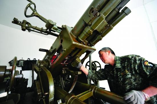 图为工作人员在检修高炮。