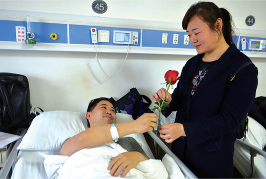 病房内,刘静送妻子玫瑰花