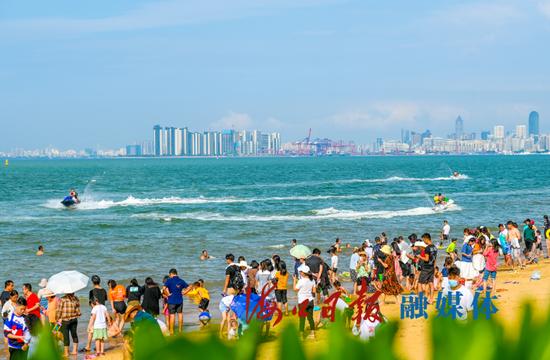 5月1日,不少市民游客携家带口来到海口假日海滩,或漫步沙滩、或乘风破浪。海口日报记者 石中华 摄