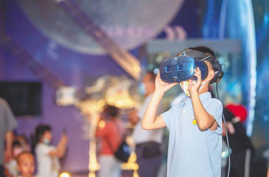 """4月24日,在海南省博物馆,市民观看""""扬帆起航 逐梦九天""""中国航天科技成果展。 本报记者 袁琛 摄"""