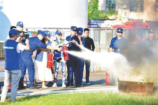 记者在消防救援人员的协助下体验消防项目。 邱肖帅 摄