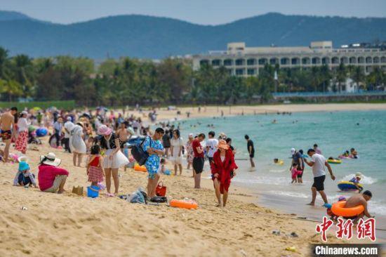 资料图。图为三亚大东海旅游景区的沙滩吸引了许多游客前来游玩。 骆云飞 摄