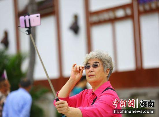 11月11日,一银发游客在三亚南山文化旅游区游览、自拍。 陈文武摄