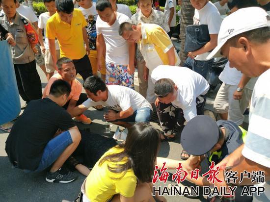 ↑10月6日,一名广东女游客在三亚街头昏倒,众人出手救助。