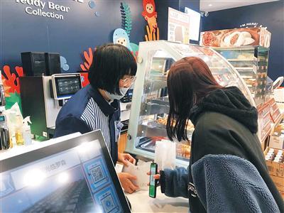 王娜服务深夜来便利店购物的顾客。记者郭萃 摄