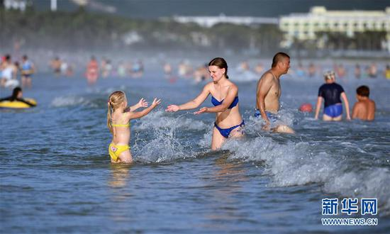 8月30日,一名外国游客带着孩子在三亚大东海戏水。新华社记者郭程摄