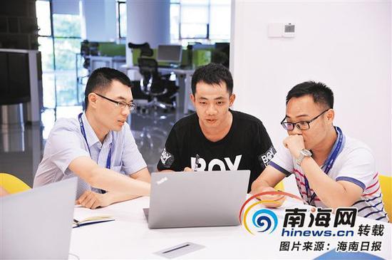 6月11日下午,海南生态软件园集团公司,曾任职于海尔集团的上海大学研究生王绪传(左一),曾任职于华为、IBM等企业的清华大学研究生孙江宇(中)和同事讨论工作。通讯员杨裕宁摄