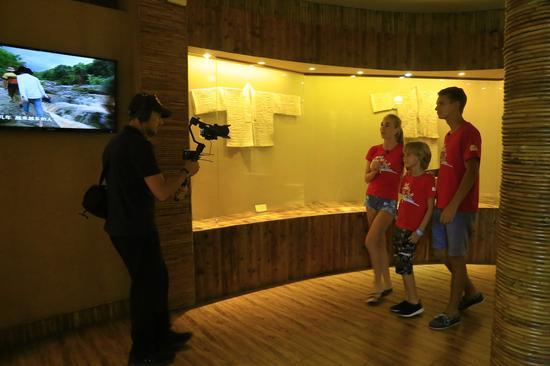白俄罗斯旅游达人在景区展馆中观光黎族纺织武艺