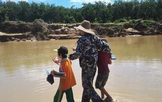 儋州:农场进出桥被冲断 父母背孩子过河