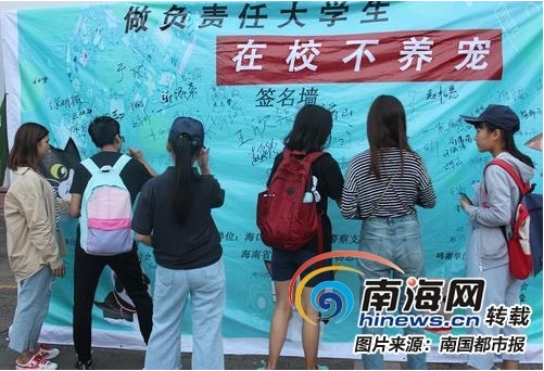"""""""在校不养宠""""公益宣传活动中,大学生签名承诺。(海南省众善关爱小动物志愿者协会供图)"""