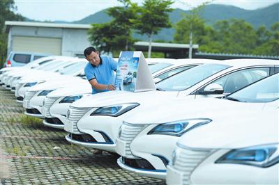"""8月12日,停放在吉阳大道海南智车慧汽车服务有限公司准备""""上线""""的新能源汽车。记者袁永东摄"""