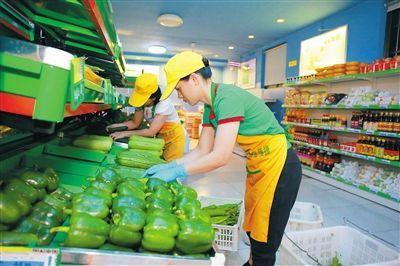 """9月12日凌晨,在海口市秀英区""""菜篮子""""社区平价菜店东方洋网点,工作人员将刚配送到的蔬菜摆上货架。 见习记者 李天平 摄"""
