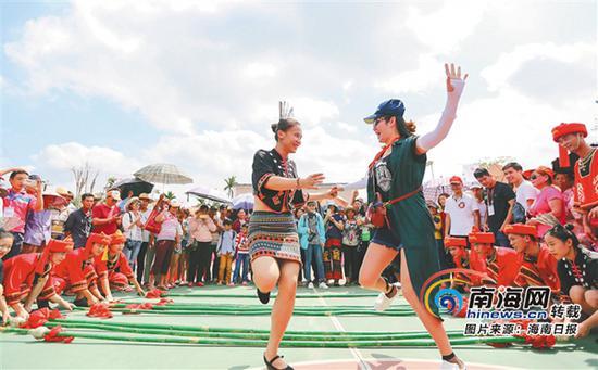 游客在陵水黎族自治县文罗镇坡村体验竹竿舞。本报记者武威 通讯员陈思国摄