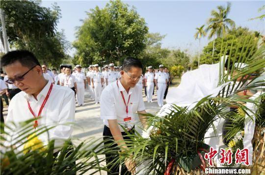 参加活动陵水县领导干部、驻陵部队军官整理花篮缎带。 陈思国 摄