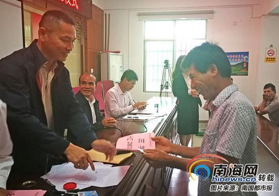 三亚市吉阳区罗蓬村村民兰学明领到分红款。