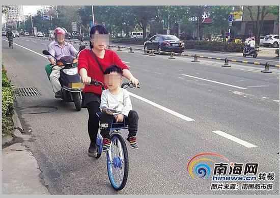 少儿坐在前车筐里。 (1月7日,拍摄于琼海兴海中路)