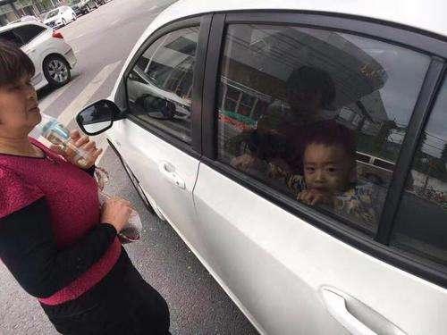 武汉一女子不慎将儿子反锁车内 消防员紧急破窗救人