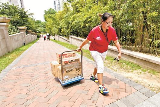 图为硚口区女快递员廖红霞拉着拖车为客户送件 新华社发