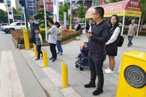 """装在人行道边上的""""神器"""",行人闯红灯越线,黄桩便会朝行人喷出水雾警告。大冶市公安局供图"""