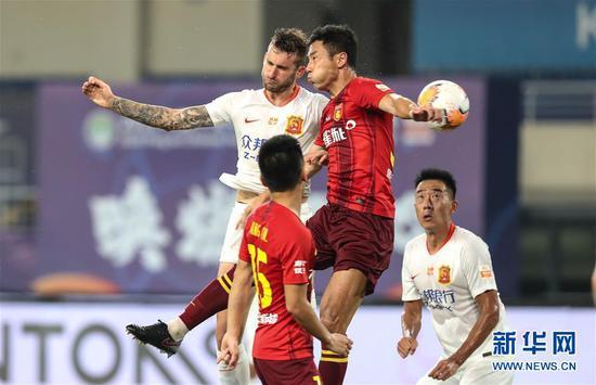 8月21日,武汉卓尔队球员巴普蒂斯唐(上左)在比赛中争顶。 当日,在2020赛季中国足球协会超级联赛第一阶段(苏州赛区)第六轮比赛中,武汉卓尔队以1比3负于河北华夏幸福队。 新华社记者杨磊摄