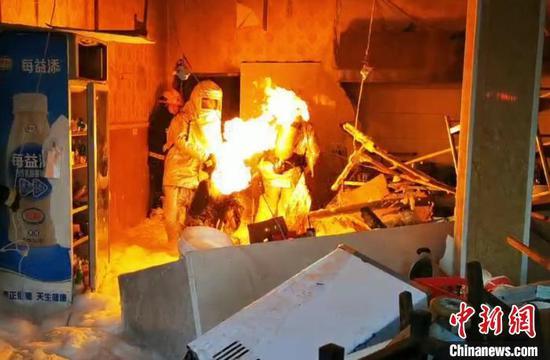一名消防救援人员在泡沫水枪掩护下,三进厨房拎出煤气罐。湖北咸宁消防供图