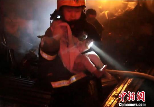 救火员用衣物捂住被困小孩口鼻,将其抱送至安好地区 刘芳琳 摄