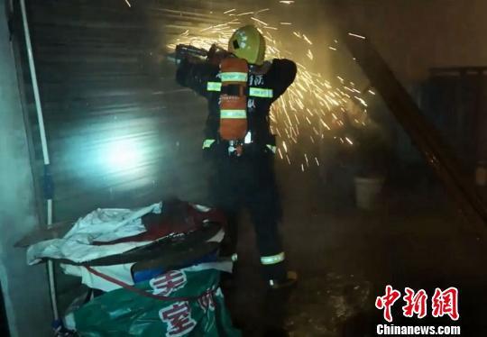 救火员使用无齿锯将卷帘门破拆 刘芳琳 摄