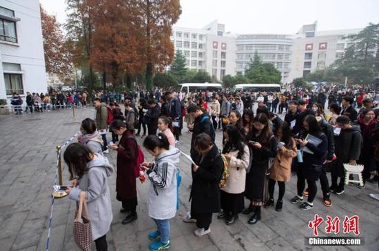 资料图:图为2018年12月2日,考生在2019国考南京林业大学考点等候进场参加考试。中新社发 苏阳 摄 图片来源:CNSPHOTO