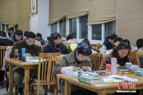 资料图:2019年11月25日,贵州民族大学逸夫图书馆内,考研学生正在看书复习,为2020年全国硕士研究生招生考试做准备。中新社记者 瞿宏伦 摄