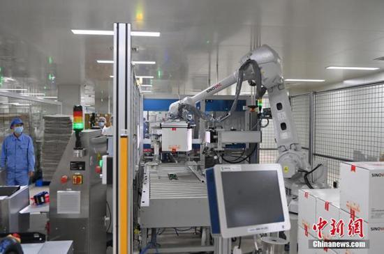 6月1日,位于北京市大兴区的北京科兴中维生物技术有限公司新冠疫苗包装生产线上,5月中旬投用的码垛机器人正在作业。据公司工作人员介绍,未来还将有至少6条包装生产线投用码垛机器人,以提高作业效率。中新社记者 侯宇 摄