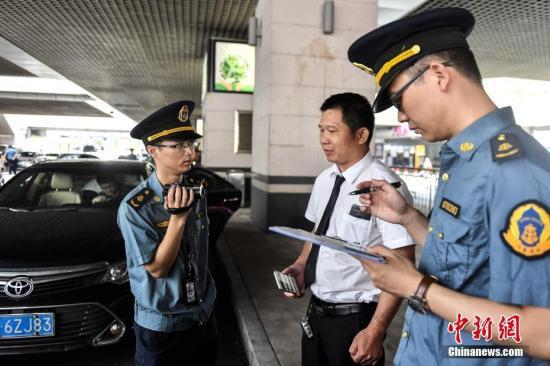 5月16日,广州市交通委员会执法局执法人员在广州东站对网约车相关资质进行核查。中新社记者 陈骥旻 摄