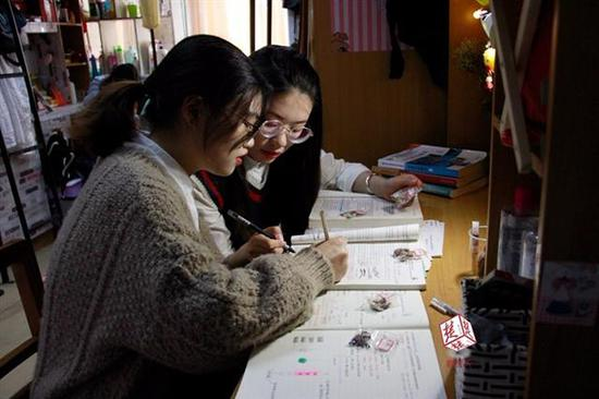 朱雯燕(左)和王华君对照书本标注药材的功效