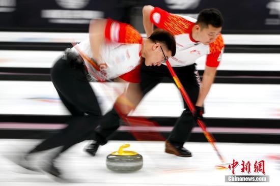资料图:中国队许静韬(左)、巴德鑫在比赛中擦刷冰面。中新社记者 富田 摄