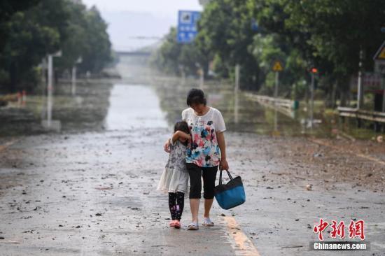 连日来,衡东县出现了持续强降雨天气,造成该县17个乡镇、233个村、22个社区普遍受灾。图为两位村民在东健大道上折返回家。(资料图片)杨华峰 摄