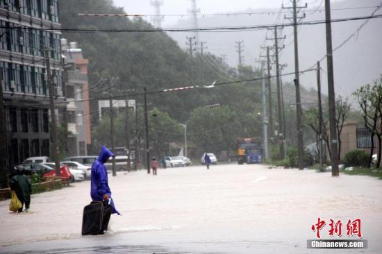 8月10日,浙江温岭,当地村民正步行通过积水路段。中新社发 金云国 摄