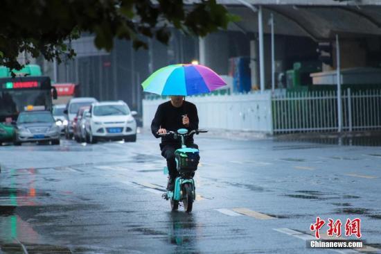资料图:市民冒雨出行。中新社记者 王中举 摄